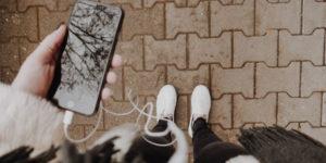 Foto de uma pessoa segurando o celular e escutando o fone de ouvido